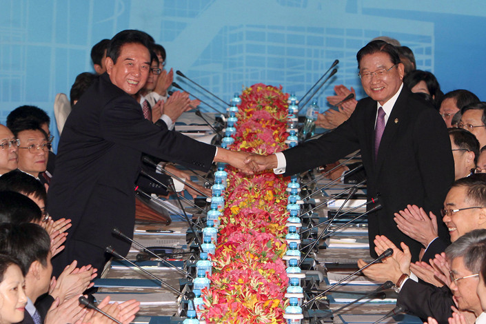 The late Chiang Pin-kung (right), chairman of Taiwan's Straits Exchange Foundation, shakes hands with his counterpart Chen Yunlin on the second day of cross-strait negotiations in August 2012 in Taipai. Photo: IC