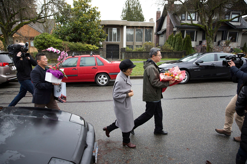 Individuals with flowers exiting a consular vehicle arrive at Meng's residence on Dec. 12. Photo: VCG