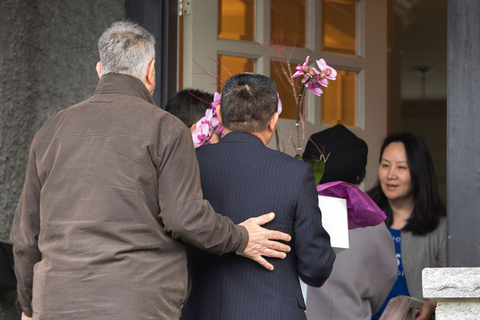 Individuals who arrived in a consular vehicle carry flowers to the residence of Huawei Technologies Chief Financial Officer Meng Wanzhou after she was released on bail in Vancouver on Dec. 12. Photo: VCG