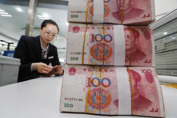 Bank employees count money in Lianyungang, Jiangsu province. Photo: VCG