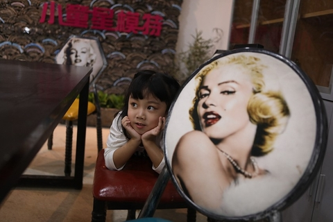 A girl poses for photos beside a picture of Marilyn Monroe in Huzhou on Oct. 27. Photo: VCG