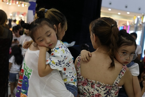 A girl sleeps on her mother's shoulder after modeling classes on July 13. Thousands of children take modeling classes in Huzhou. Photo: VCG