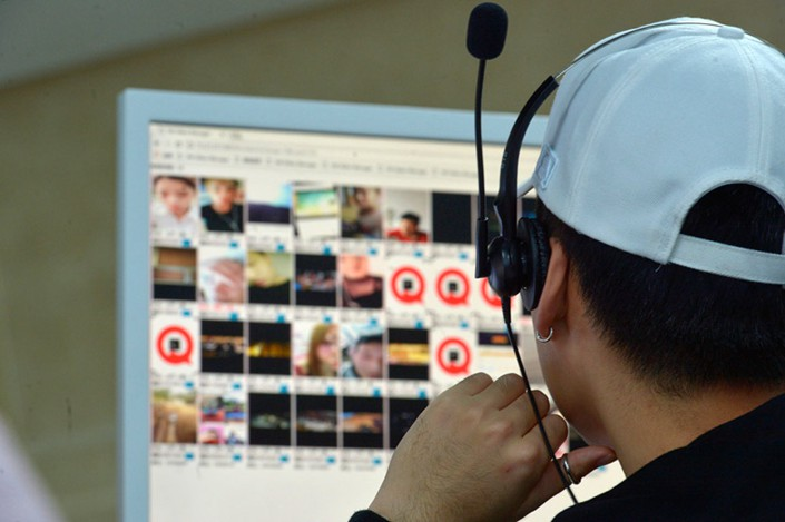 A content moderator listens to voice messages in Yuwan's office in Guiyang, Guizhou province, Sept. 14, 2018. Photo: VCG