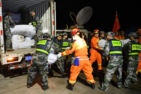 Police and militia unload relief supplies at a temporary shelter in Yibin, Sichuan province, on Sunday, hours after a strong earthquake rattled the city. Photo: VCG