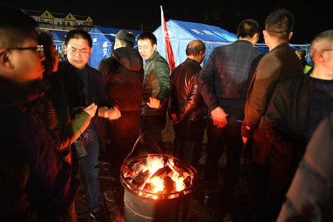 Earthquake victims in Yibin, Sichuan province, gather around a fire at a temporary settlement for warmth on Monday. Photo: VCG