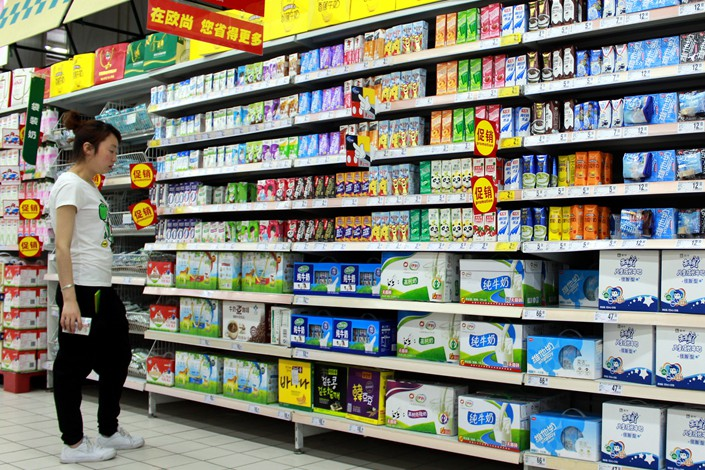 Supermarket customers examine milk in the dairy-products section of a supermarket in Nanjing, Jiangsu province, on June 4. Photo: VCG