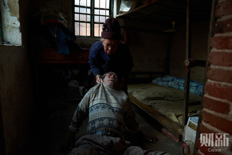 Zhang Guifang, 84, who lives with her 64-year-old paralyzed son, Huang Jinqiang, in Tengshan village, Guangdong province, hoists her son out of bed every morning and drags him to where he sits and then drags him back before sunset. Her story reflects the plight of many parents of disabled people. According to the China Disabled Persons' Federation, 45% of the country's 85 million people living with disabilities were over 65 years old in 2006. Photo: Liang Yingfei/Caixin