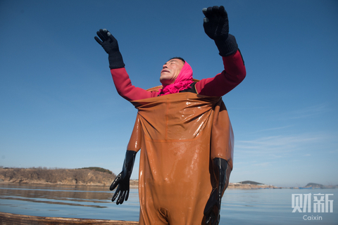 Ning Hai, a 44-year-old sea cucumber harvester, takes off his diving suit after collecting sea cucumbers in the freezing water near Guanglu Island, Dalian, Northeast China's Liaoning province. Harvesting sea cucumbers, an expensive delicacy, is a tough and dangerous job, but wages have not kept pace with inflation in recent years. Most of Ning's colleagues are in their 40s now, and their livelihoods are threatened by the industry's increasing mechanization. Photo: Chen Liang/Caixin