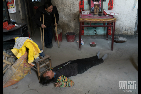 Ou Xiangbin's mother cries on the floor after dreaming of her son who fell to his death while climbing down a rope to leave the roof of a building he was working on in Zhengzhou, Central China's Henan province, on Feb. 3. Ou and his co-workers were supposed to use a ladder, but it had been removed by urban patrol officers who claimed it was their duty to take away tools that violated regulations. Photo: Chen Weixi/Caixin