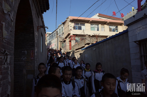 Students from No. 3 Middle School in Mizhi county pass through a narrow alley to leave school in Shaanxi province on May 2. Five days earlier, a man armed with a knife stabbed 19 students at the school, killing nine. Photo: Ding Gang/Caixin