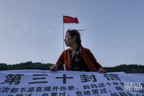 Cheng Xingfeng, the mother of a Maoba Middle School student who has been missing since the 2008 Sichuan earthquake, carries the 30th banner she has placed on the ruins of the school on May 12, the 10th anniversary of the earthquake. The earthquake killed nearly 70,000 people in two minutes, injured 370,000 and left nearly 20,000 missing. Photo: Liang Yingfei/Caixin