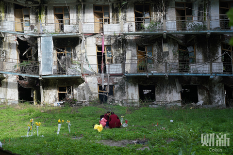 A family of three mourns their dead relatives on May 12 in front of a building damaged during the 2008 Sichuan earthquake. Photo: Liang Yingfei/Caixin