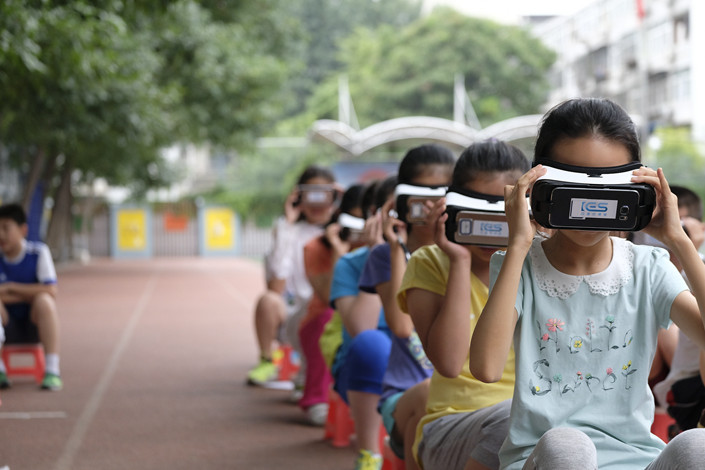 Beijing elementary school students wear virtual reality headsets during an astronomy lesson on June 23. Photo: VCG