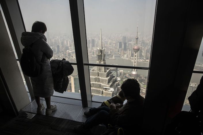 People look at the view from the observation deck at the Shanghai World Financial Center as the Jin Mao Tower