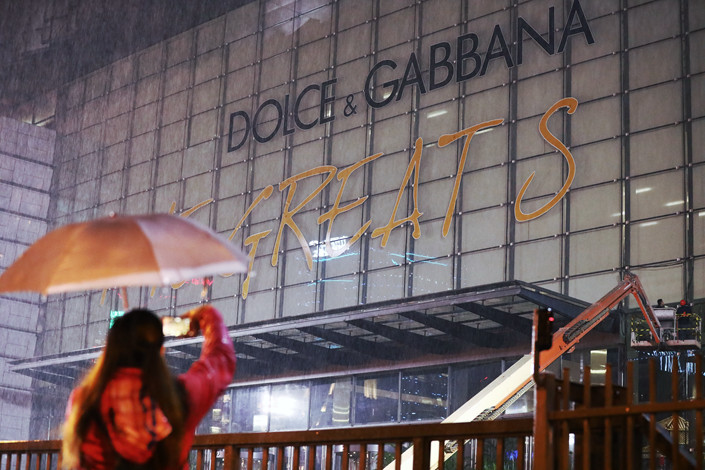A worker takes down the sign a Dolce & Gabbana fashion show in Shanghai on Nov. 21. Photo: IC