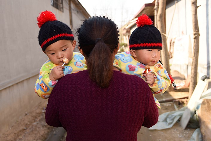A mother holds her twin sons in Rizhao, East China's Shandong province on March 9. Photo: IC