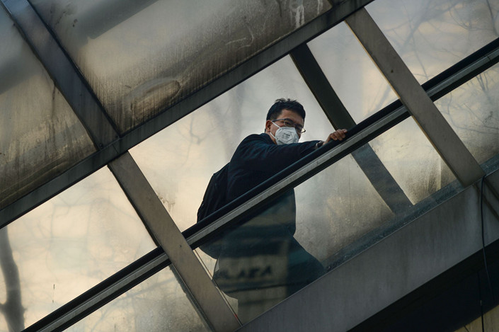 A man wearing a face mask rides an escalator to cross an overpass in Beijing on Dec. 19. Photo: VCG