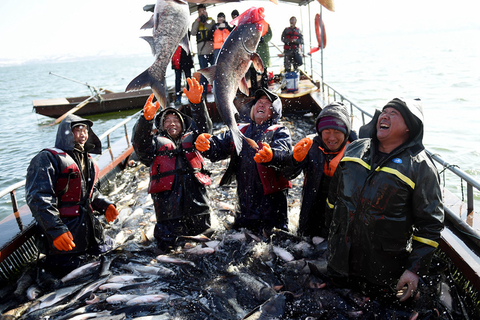Fishermen cheer the successful fishing harvest — more than 10 tons — during the winter fishing festival in Luoyang, Henan province, on Jan. 29, 2018. Photo: VCG