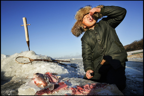 A member of China's Hezhe ethnic group eats raw fish after catching it from an icy lake in Jinjiekou, Heilongjiang province, on Jan. 3, 2007. Photo: VCG