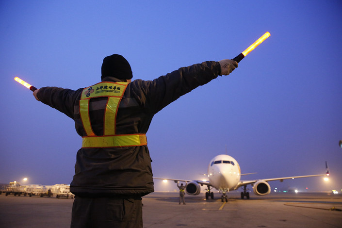A member of Xi'an Xianyang International Airport's groundcrew signals to a plane. Photo: VCG
