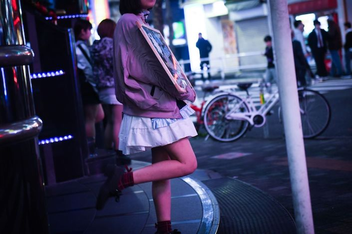 A woman holds an advertisement for a girls bar in the Shinjuku ward of Tokyo. Photographer: Noriko Hayashi/Bloomberg
