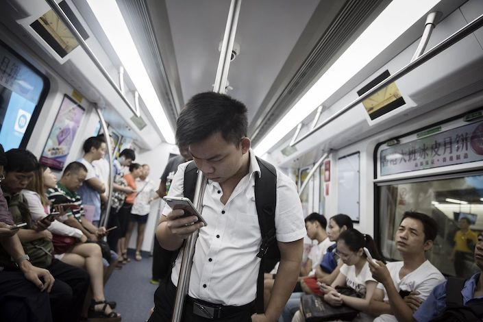 A passenger looks at a smartphone on a subway train in Shenzhen. Photo: Bloomberg