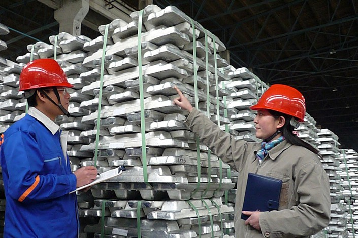 Technicians carry out quality tests on aluminum ingots for export at the Guangxi branch of the Aluminum Corporation of China on Feb. 1, 2018. Photo: VCG