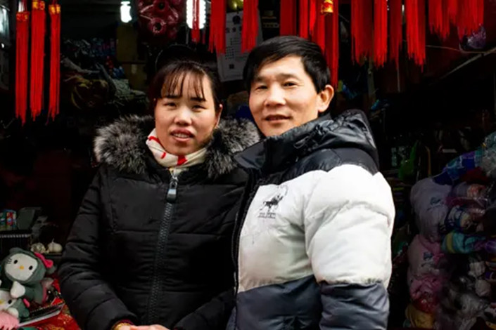 Wu Xia her husband Sun stand outside their shop in downtown Shanghai. This year the cheery kaleidoscope of red and gold hanging outside her store masks the subdued mood of many of China's small business owners. Photo: Grainne Quinlan/AFR