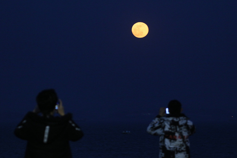 Two people take photos of the supermoon in Yantai, East China's Shandong province on Jan. 21. Photo: VCG