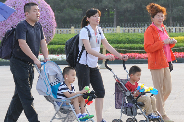 Parents push strollers with their children in Tiananmen Square in Beijing. Photo: VCG