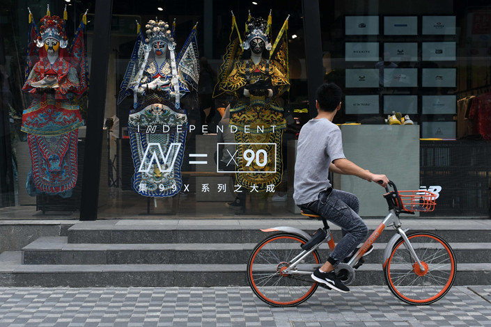 A man rides a Mobike bicycle past a New Balance store in Beijing on Sept. 1. Photo: VCG