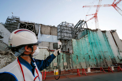 An employee of Tokyo Electric Power Co. measures radiation levels during decommissioning work Wednesday at reactor Unit 4 of the company's Fukushima Dai-ichi Nuclear Power Plant in Okuma, Fukushima prefecture, Japan. The nuclear power plant was devastated on March 11, 2011, by a tsunami that followed a magnitude 9.0 earthquake. Photo: IC