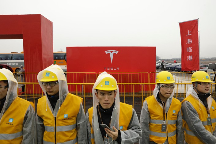 Workers in rain gear wait ahead of an event at the site of the Tesla manufacturing facility in Shanghai on Jan. 7. Photo: VCG