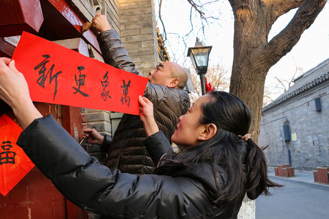 A woman places a couplet on the top of a door to decorate her house and celebrate the Spring Festival in Beijing on Monday. Photo: VCG