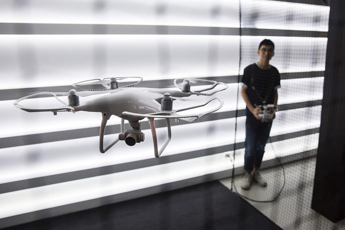An employee of DJI Technology Co. Ltd. demonstrates a company-made drone at the grand opening of DJI's flagship store in the Causeway Bay district of Hong Kong in September 2016. Photo: VCG