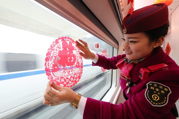 An attendant decorates the window of a train from Chongqing to Guiyang on Jan. 29, 2019. Photo: VCG