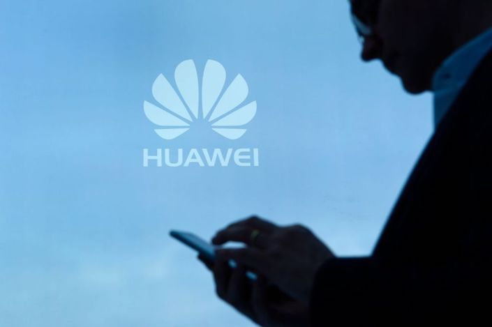 A visitor uses his mobile phone at the Huawei stand on the second day of the Mobile World Congress on February 28. Photo: Bloomberg