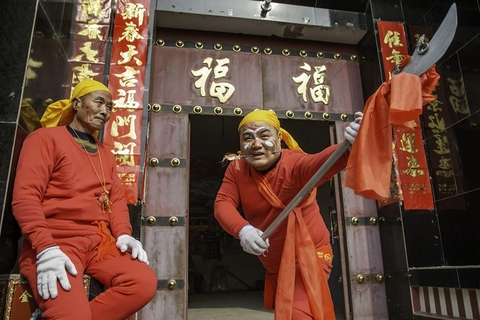 A performer holding a pole-arm displays an iron spike stabbed through his cheek in Yuncheng, Shanxi province, on Feb. 8. Local residents believe that stabbing one's cheek with such a spike during the Spring Festival will bring them luck and longevity. Photo: VCG