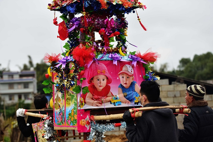 Villagers in Shanxi province carry a structure decorated with symbolic objects and photos of babies as part of a traditional celebration intended to bring luck in the new year. Photo: VCG