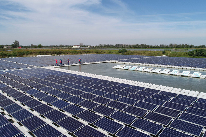 Workers inspect equipment at a floating solar power station in Anhui province on Oct. 15, 2018. Photo: VCG