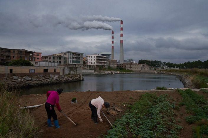 Two elderly women work on a small piece of farmland near a thermal power plant in Kecuo village in Quanzhou, Fujian province, on Nov. 13. Photo: Liang Yingfei/Caixin