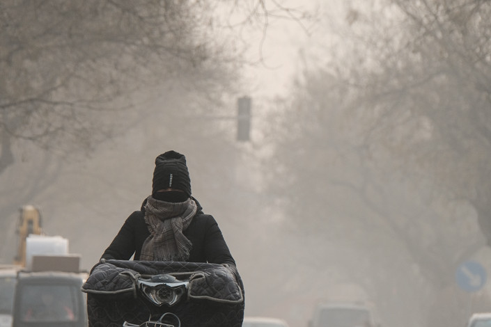 A commuter wearing a face mask rides through heavy smog in Beijing on Jan. 14. Photo: IC