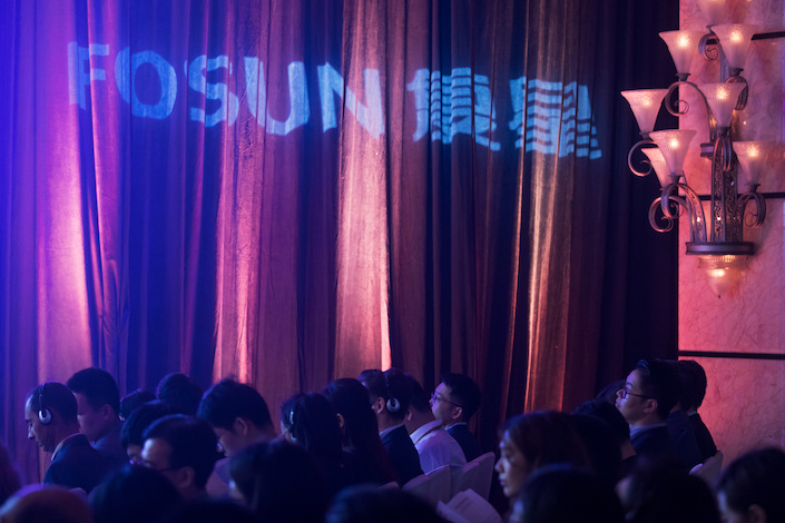 Fosun International branding is projected on a curtain during a news conference in Hong Kong. Photo: VCG