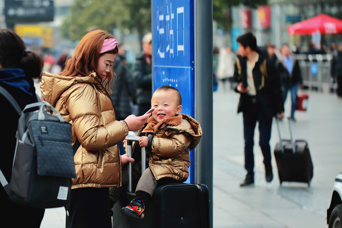 A mother prepares to travel with her child at Shanghai Hongqiao Railway Station. Photo: IC