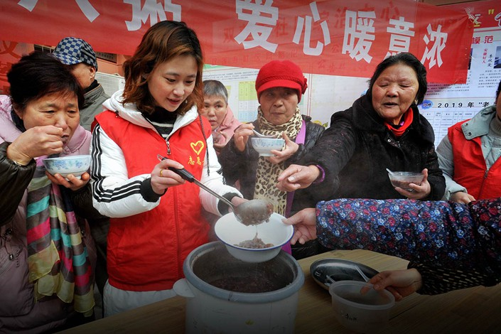 A party member serves porridge to local residents during the Laba festival in Anqing, Anhui province, on Jan. 13, 2019. Photo: VCG