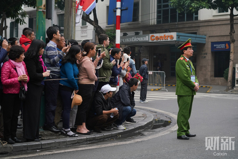 People wait to catch a glimpse of the vehicle carrying Kim Jong Un. Photo: Caixin/Liang Yingfei