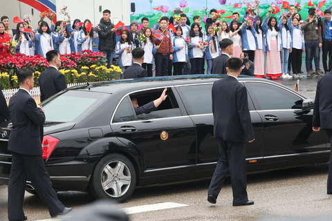 Kim Jong Un gets in a limousine as children wave Vietnamese and North Korean flags on Tuesday. Twelve bodyguards surrounded the car before it started. Photo: VCG