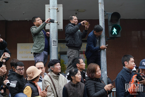 People take photos of the fleet of vehicles carrying Kim Jong Un and his entourage. Photo: Caixin/Liang Yingfei
