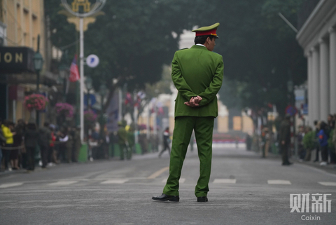 A local police officer stands guard at the crossing where the vehicle carrying Kim Jong Un will pass in Hanoi. Photo: Caixin/Liang Yingfei