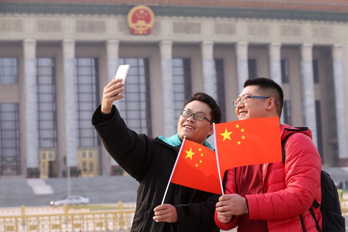 Tourists take selfies against the backdrop of Beijing's Great Hall of the People, where the Two Sessions are held, on Feb. 28. Photo: IC